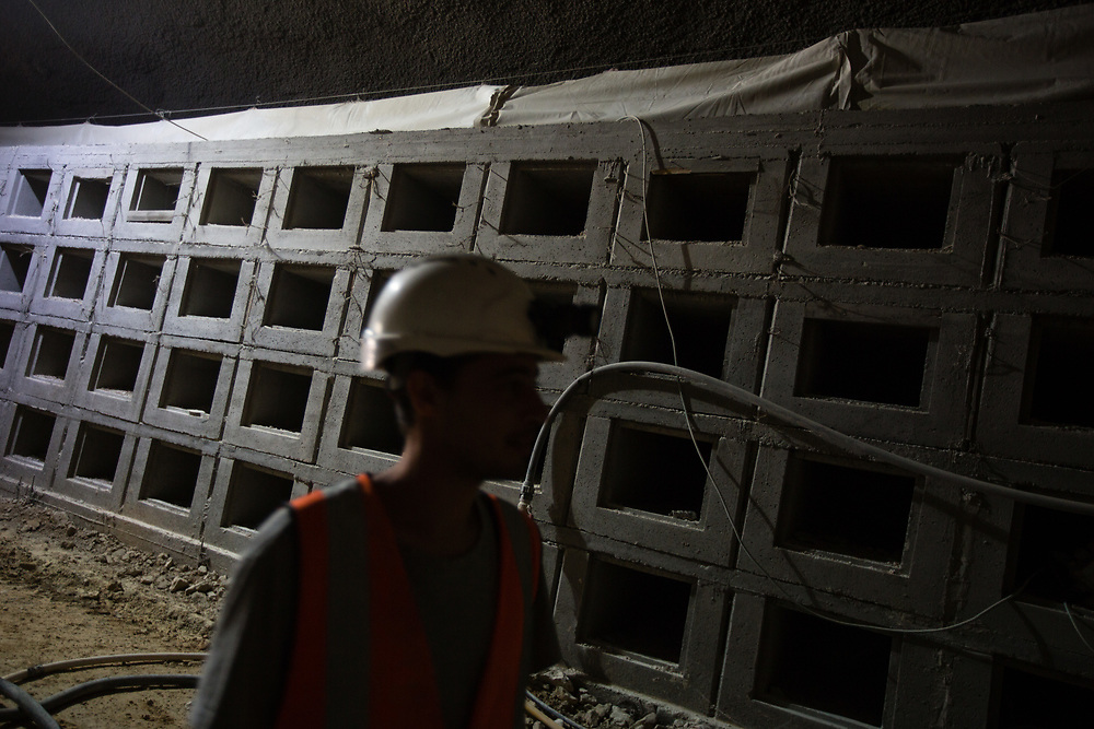 A worker is seen in front of partially constructed notched burial plots at the construction site of an underground tunnel designated for traditional Jewish burial at the Givat Shaul cemetery, in Jerusalem, Israel, on May 14, 2015.