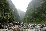 A river tracer navigates through a narrow river valley near Taroko Gorge, Taiwan.
