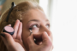 Makeup artist applying make up brush near eye, Munich, Bavaria, Germany