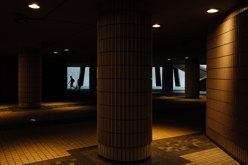 People are silhouetted as they walk through a passage outside the Hong Kong Cultural Centre in Tsim Sha Tsui, Kowloon, Hong Kong, China, on September 25, 2019.