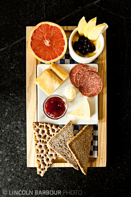 A breakfast board of crackers, jam, fruit, smoked meats, and cheeses