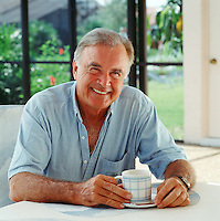 man with morning coffee.sitting in sunny  screened porch,