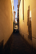 A narrow Italian alleyway is shaded from the bright sun