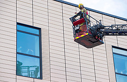 © Licensed to London News Pictures; 30/04/2020; Bristol, UK. Avon Fire and Rescue erect an extendable ladder outside the Intensive Care Unit at Southmead Hospital as staff wave from the ICU windows and Emergency Service workers and the public clap outside Southmead Hospital at 8pm on Thursday evening to applaud NHS health service workers during the coronavirus Covid-19 pandemic. Photo credit: Simon Chapman/LNP.