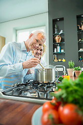 Portrait of mature couple preparing food in kitchen, smiling