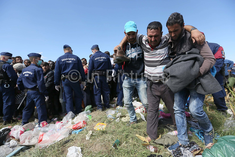 Migrants  break through a police corden to board a bus close to the Hungarian and Serbian border town of Roszke, Hungary, September 7 2015. The UN's humanitarian agencies are on the verge of bankruptcy and unable to meet the basic needs of millions of people because of the size of the refugee crisis in the Middle East, Africa and Europe, senior figures within the UN have told the media.