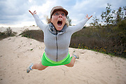Young woman pulls a face while jumping in the air
