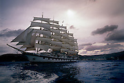 A clipper ship sails at sunset across the Mediterranean Sea, off the coast of Italy