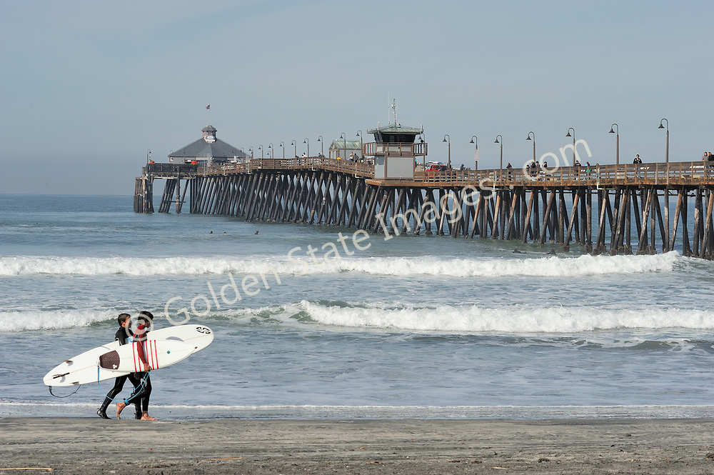 Surfers walk along the beach just south of the pier.<br /> <br /> The original Imperial Beach pier was built in 1909. It was constructed to generate electricity from wave action for the town. The massive machinery located on the end of the pier was called the Edwards Wave Motor. It proved to be a failed experiment and was later removed. The last of the original pier was destroyed by a winter storm in 1948.
