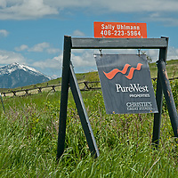 A real estate sign hangs in a field near Bozeman in Montana's Gallatin Valley.  The Bridger Mountains rise in the background