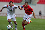 Craig Bellamy of Wales battles for the ball with Kim Kintziger of Luxembourg.  friendly international match, Wales v Luxembourg at the Parc y Scarlets stadium in  Llanelli on Wed 11th August 2010. pic by Andrew Orchard, Andrew Orchard sports photography,