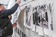 """Portland, Oregon, USA. 26 FEB, 2018. The photographer Robert Frank's work from his ground breaking book """"The Americans"""" hangs  defaced as a gallery goer shreds it at Blue Sky Gallery in Portland, Oregon, USA. The work was destroyed in a """"Destruction Dance"""" performance defacing the photographs with ink and mutilation with scissors, knives and even ice skates  at the end of it's run. The destruction was Frank's protest regarding today's greed in the global art market."""