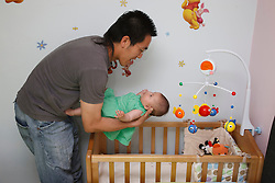 Chinese father putting his baby daughter to bed