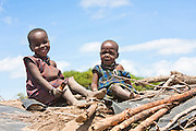 2 Maasai children on the roof of a hut. Photographed in Kenya