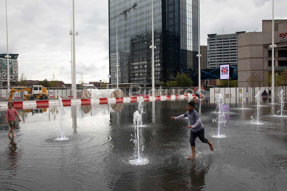 Local people interacting with the new fountains in Centenary Square in Birmingham, United Kingdom. The £16m redevelopment of Birminghams Centenary Square has now been formally opened. Paradise, formerly named Paradise Circus, is the name given to an area of approximately 7 hectares in Birmingham city centre between Chamberlain and Centenary Squares. The area has been part of the civic centre of Birmingham since the 19th century. From 2015 Argent Group will redevelop the area into new mixed use buildings and public squares.