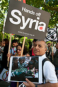 Demonstration against any intervention in Syria called by Stop the War and CND, August 30th 2013, Central London. A man holds a photo of the funeral procession of a small child.
