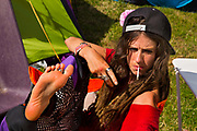 Glastonbury Festival, 2015.<br /> Girl camping  relaxing with roll up cigarette