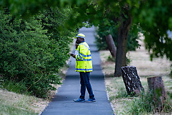 © Licensed to London News Pictures. 07/06/2020. London, UK. A police officer talks on a phone next to a cordon around Fryent Country Park. The bodies of two women have been found in Fryent Country Park in Wembley. Metropolitan Police Service were called at 13:08 BST, Officers found two unresponsive woman, they were pronounced dead at the scene. Photo credit: Peter Manning/LNP