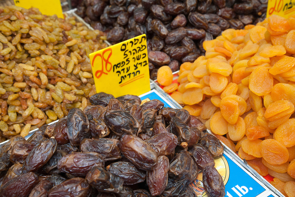 """Middle East, Israel, Jerusalem,  dates and other dried fruits on display at Mahane Yehuda Market (also known as Machaneh Yehuda), often referred to as """"The Shuk"""", is popular with locals and tourists alike, the market's more than 250 vendors sell fresh fruits and vegetables; baked goods; fish, meat and cheeses; nuts, seeds, and spices; wines and liquors; clothing and shoes; housewares, textiles, and even Judaica."""
