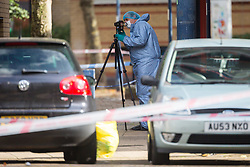 A forensic officer examine photographs the scene following the murder on October 17th of Ian Tomlin, 46, at the high-rise Doddington Estate in Battersea, South London . Battersea, London, October 18 2018.