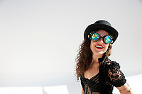 Happy woman wearing a bowler hat and black lace with prism goggles.