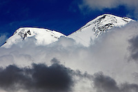 Russia, Caucasus, Mount Elbrus, highest mountain of Europe (5642 m asl), seen from Mount Cheget in the morning. The mountain has two summits, the left summit is the highest. Mountains surrounded by clouds.