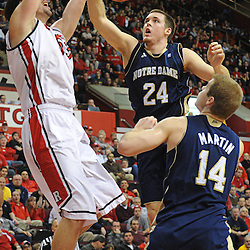 Rutgers Scarlet Knights forward Gilvydas Biruta (55) slam dunks a basket past Notre Dame Fighting Irish guard/forward Pat Connaughton (24) and guard Scott Martin (14) during Big East NCAA action during Rutgers' 65-58 victory over Notre Dame at the Louis Brown Athletic Center in Piscataway, N.J.