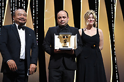 """Guatemalan director Cesar Diaz (C) delivers a speech flanked by French-Italian actress Valeria Bruni Tedeschi (R) and Cambodian director and President of the Camera d'Or Jury Rithy Panh after he was awarded with the Camera d'Or for his film """"Our Mothers (Nuestra Madres)"""" on May 25, 2019 during the closing ceremony of the 72nd edition of the Cannes Film Festival in Cannes, southern France. Photo by David Niviere/ABACAPRESS.COM"""