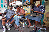 Suva, Fiji | 2011<br /> Roneel Chand (center) repairs shoes at a stall in downtown Suva, while his family grows cash crops on leased land in nearby Navua. He is the primary earner in his family, making, he says, up to FJD 100 (USD 50) a day repairing shoes.