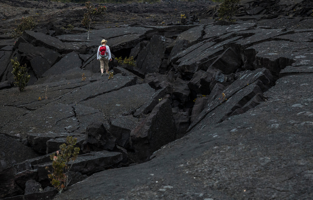 A woman stands on the cracked and fallen in lava of floor of  Kilauea Iki crater, Hawaii Volcanoes National Park, Hawai'i, USA