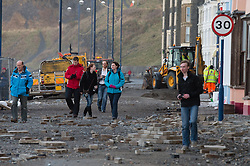 © Licensed to London News Pictures. 07/01/2014. Aberystwyth, UK. As the stormy weather subsides, the full impact of several days of huge tides and massive waves becomes clear to see on Aberystwyth promenade, Wales UK. People walk amongst the rubble as workmen begin the long process of clearing up the debris and making the area safe and secure. Photo credit : Keith Morris/LNP