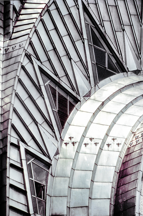 A tight close-up of the triangular windows and stainless steel, Art Deco crown of the Chrysler Building