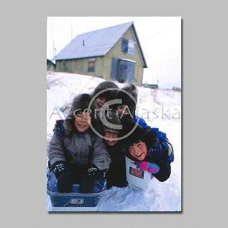 Alaska. Koyuk Village. Young eskimo boys play in snow with makeshift sled.
