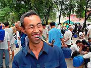 Man with pipe at bird market, Duyun, Guizhou Province, China.