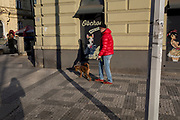 A pet owner walks his dog past a canine business on Milady Horakove street, Holesovice district, Prague 7, on 19th March, 2018, in Prague, the Czech Republic.