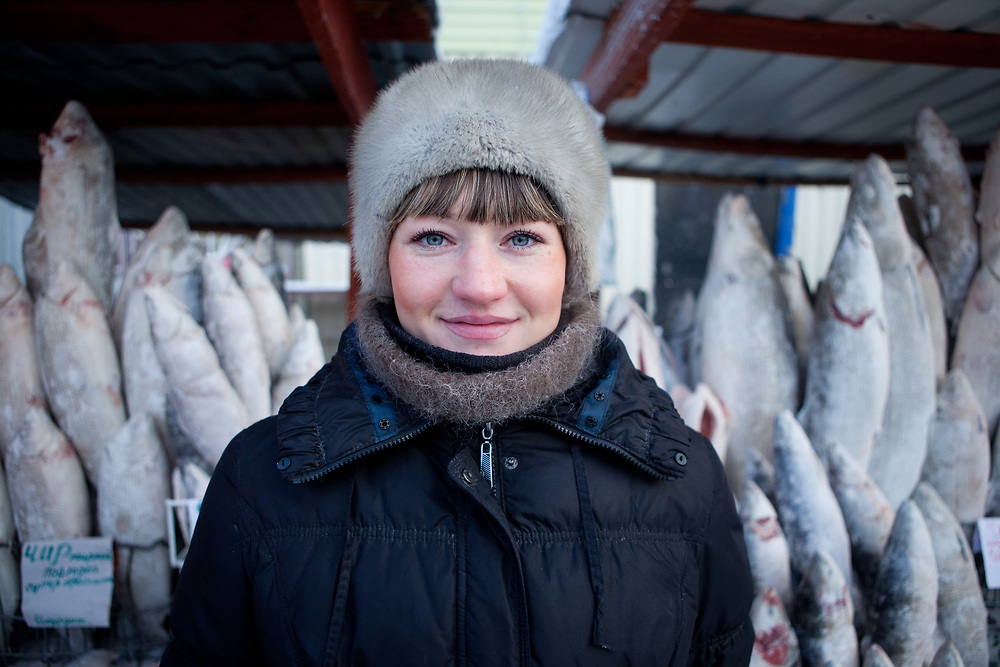 Portrait of a women selling frozen fish on the Yakutsk outdoor fish market. Yakutsk (Russian: Яку́тск) is a city in the Russian Far East, located about 4° (450 kilometres) south of the Arctic Circle. It is the capital of the Sakha (Yakutia) Republic in Russia with a major port on the Lena River. The city has a population of 264.000 (2009). Yakutsk is one of the coldest cities on Earth. The average monthly winter temperature in January is around −43,2 °C. Yakutsk, Jakutsk, Yakutia, Russian Federation, Russia, RUS, 16.01.2010.