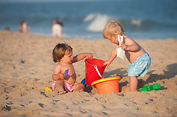 two boys enjoying playing with pails and shovels at the beach in East Hampton, NY