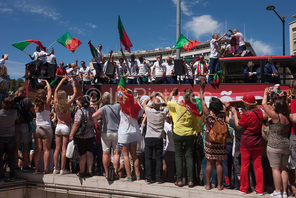 Thousands of Portuguese sports fans cheer their national football team bus as it passes-by during their victory procession through the capitals streets, the day after the Euro 2016 final with France, on 11th July 2016, in Lisbon, Portugal. Waving flags and voicing their love for the team in Praca Marques de Pombal in the largely corporate and banking district of the city, they take photos and cheer their favourite players, including the national hero/deity, Christiano Ronaldo.
