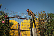 An Algerian man scales the fence surrounding the international port in Patras, hopeful to hide on a boat heading to Italy. Patras, Greece. October 2010