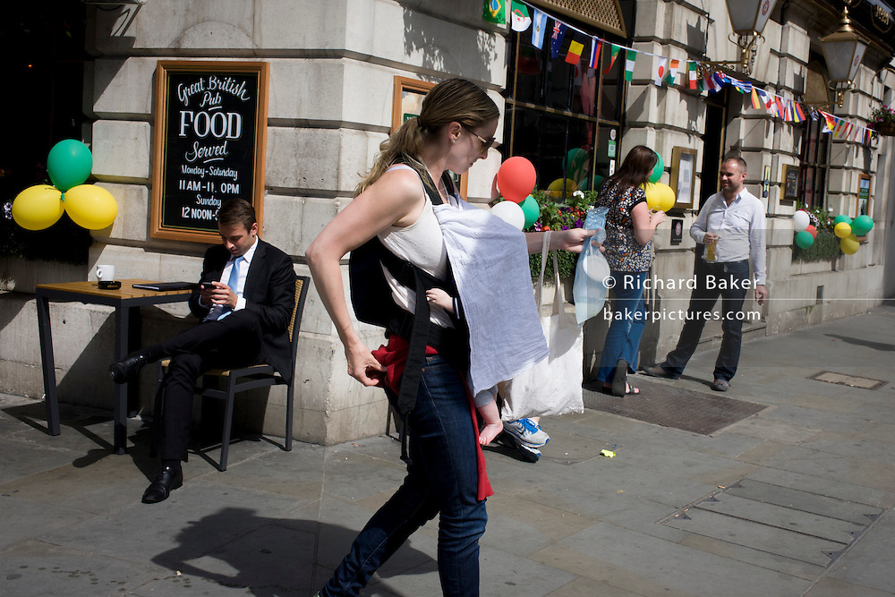 Young mother carries shaded baby covered in sheet, past a street corner pubin central London.