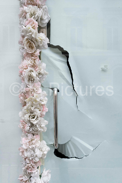 A close-up of a door handle and the torn paper that obscures the interior of a retail business, closed since the Coronavirus pandemic lockdowns when none other than essential shops closed, on 29th April 2021, in London, England.