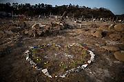 Ishinomaki  Quartier Minami Hamacho  commémoration   mars 2012.Il ne reste plus rien du quartier résidentiel Minami Hamacho. Sétendant sur des kilomètres, des bouquets de fleurs sont placés par les familles sur lemplacement des maisons ou sur les lieux où leurs proches ont été retrouvés.
