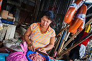 08 JANUARY 2007 - MANAGUA, NICARAGUA:  A woman cuts up sausage in her stand in Mercado Oriental, the main market that serves Managua, Nicaragua. The market encompasses dozens of square blocks and is the largest market in Central America.  Photo by Jack Kurtz