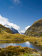 Trampers pass the tarn (pond) atop MacKinnon Pass, along the Milford Track, Fiordland National Park, New Zealand