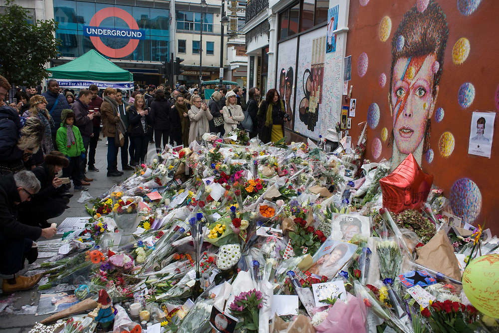 The growing shrine to musical artist David Bowie in Brixton, south London, the place of his birth in 1947. Fans of iconic English music artist David Bowie who died from Cancer at the age of 69 on Sunday 10th January, gather to pay their respects at a makeshift shrine of flowers and tributes to the local boy from Brixton, south London. Commuters stopped-by before entering the nearby underground station to take pictures and silently remember their hero's great days playing the soundtracks of their childhoods.