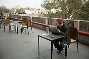 A man reads a newspaper on the roof terrace of the Indian Coffee House, Baba Kharak Singh Marg, New Delhi, India.The Coffee House dates back almost fifty years, first in central Connaught Place, then Janpath and now at the top of a rather shabby shopping centre. Still run by the Indian Coffee Workers Cooperative Society, it was a regular haunt for politicos in Delhi and It's clientelle is still well read and intellectual.