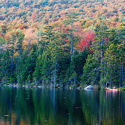 A man canoeing on Pond of Safety in the Randolph Community Forest. in New Hampshire's White Mountains.