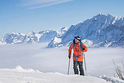 Skier climbing snow mountain in Upper Bavaria, Germany, Europe