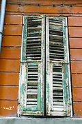 Old weathered wooden shutters on an orange wall