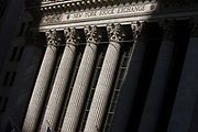 Classical pillars and American flag hanging in front of the New York Stock Exchange (NYSE) on Wall Street, Lower Manhattan. This famous street symbolises the US economy. Wall Street is a 0.7 miles (1.1 km), eight-block-long, street running west to east from Broadway to South Street on the East River in Lower Manhattan in the financial district of New York City. Over time, the term has become a metonym for the financial markets of the United States as a whole, the American financial sector or signifying New York-based financial interests. The NYSE is world's largest stock exchange by market capitalization of its listed companies at US$16.613 trillion as of May 2013. Average daily trading value was approximately US$169 billion in 2013.